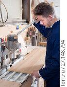 Купить «Male joiner adjusting chipboard at workshop», фото № 27148794, снято 7 ноября 2016 г. (c) Яков Филимонов / Фотобанк Лори