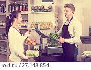 Купить «Seller assisting customer to weigh purchases», фото № 27148854, снято 23 ноября 2016 г. (c) Яков Филимонов / Фотобанк Лори