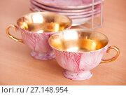 Porcelain rose and golden set of cups. Стоковое фото, фотограф Гужва / Фотобанк Лори