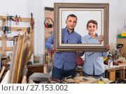 Купить «portrait of positive guy and teen displaying frame in workshop», фото № 27153002, снято 17 мая 2017 г. (c) Яков Филимонов / Фотобанк Лори
