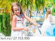 Купить «Adorable little girl with a small turtle in her hands in the natural reserve», фото № 27153990, снято 10 апреля 2017 г. (c) Дмитрий Травников / Фотобанк Лори