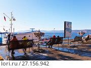Купить «Байкал. Люди сидят на скамейках и отдыхают на набережной в поселке Листвянка осенним солнечным днем», фото № 27156942, снято 29 октября 2017 г. (c) Виктория Катьянова / Фотобанк Лори