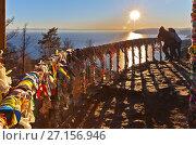Купить «Люди любуются закатом над озером Байкал из беседки с цветными ленточками туристов на скале Камень Черского над поселком Листвянка», фото № 27156946, снято 29 октября 2017 г. (c) Виктория Катьянова / Фотобанк Лори