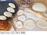 Купить «Приготовление домашних пирожков с мясной начинкой. Раскатывание теста и несколько состряпанных пирожков на листе для выпечки», фото № 27161946, снято 21 октября 2017 г. (c) Виктория Катьянова / Фотобанк Лори
