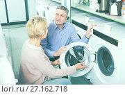 Купить «positive mature couple chooses washing machine for their house in shop of household appliances», фото № 27162718, снято 21 марта 2019 г. (c) Яков Филимонов / Фотобанк Лори