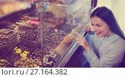 Купить «Smiling pleasant girl choosing delicious ganaches and chocolates», фото № 27164382, снято 31 марта 2020 г. (c) Яков Филимонов / Фотобанк Лори