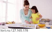 Купить «happy mother and daughter making cookies at home», видеоролик № 27165178, снято 20 августа 2019 г. (c) Syda Productions / Фотобанк Лори