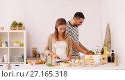 Купить «happy couple cooking food at home kitchen», видеоролик № 27165318, снято 17 июля 2019 г. (c) Syda Productions / Фотобанк Лори