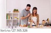Купить «happy couple cooking food at home kitchen», видеоролик № 27165326, снято 17 июля 2019 г. (c) Syda Productions / Фотобанк Лори
