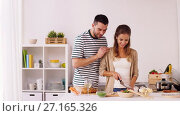 Купить «happy couple cooking food at home kitchen», видеоролик № 27165326, снято 19 ноября 2017 г. (c) Syda Productions / Фотобанк Лори