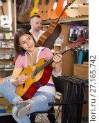Купить «Smiling girl playing professional guitar», фото № 27165742, снято 11 февраля 2016 г. (c) Татьяна Яцевич / Фотобанк Лори