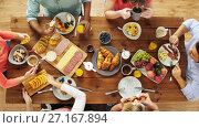 Купить «group of people eating at table with food», видеоролик № 27167894, снято 23 апреля 2019 г. (c) Syda Productions / Фотобанк Лори
