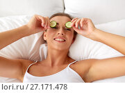 Купить «beautiful woman applying cucumbers to eyes at home», фото № 27171478, снято 9 апреля 2017 г. (c) Syda Productions / Фотобанк Лори