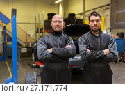 Купить «auto mechanics or tire changers at car shop», фото № 27171774, снято 21 сентября 2017 г. (c) Syda Productions / Фотобанк Лори