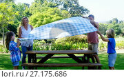 Купить «Family spreading the tablecloth on picnic table 4k», видеоролик № 27175686, снято 27 апреля 2018 г. (c) Wavebreak Media / Фотобанк Лори
