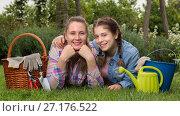 Купить «smiling young woman and girl with gardening tools in outdoors», фото № 27176522, снято 18 апреля 2017 г. (c) Яков Филимонов / Фотобанк Лори