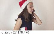 Купить «Beautiful naughty girl teenager in a Santa Claus hat emotionally communicates on the smartphone on white background stock footage video.», видеоролик № 27178470, снято 1 ноября 2017 г. (c) Юлия Машкова / Фотобанк Лори