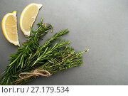 Купить «Fresh rosemary, thyme and two slices of lemon on a gray stone table.», фото № 27179534, снято 20 апреля 2019 г. (c) Olesya Tseytlin / Фотобанк Лори