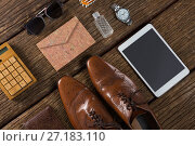 Купить «Shoes, digital tablet and sunglasses on wooden plank», фото № 27183110, снято 25 августа 2017 г. (c) Wavebreak Media / Фотобанк Лори