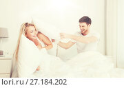 Купить «happy couple having pillow fight in bed at home», фото № 27184202, снято 25 февраля 2016 г. (c) Syda Productions / Фотобанк Лори