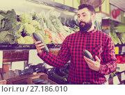 Купить «Shop assistant demonstrating zucchinis», фото № 27186010, снято 15 ноября 2016 г. (c) Яков Филимонов / Фотобанк Лори