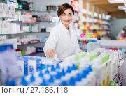 Купить «Female pharmacist arranging displayed assortment», фото № 27186118, снято 31 января 2017 г. (c) Яков Филимонов / Фотобанк Лори