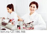 Купить «Female manicurist showing lacquer color schemes», фото № 27186166, снято 2 февраля 2017 г. (c) Яков Филимонов / Фотобанк Лори