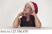 Купить «Beautiful teen girl in Santa Claus hat sitting and dreaming of a gift, expresses happiness and anticipation on white background stock footage video», видеоролик № 27186670, снято 30 октября 2017 г. (c) Юлия Машкова / Фотобанк Лори