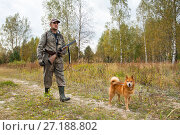 Купить «Охотник с собакой идет по лесной дороге», фото № 27188802, снято 17 сентября 2017 г. (c) Павел Родимов / Фотобанк Лори