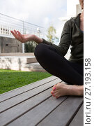 Купить «Mid section of woman practicing yoga in porch», фото № 27193158, снято 30 августа 2017 г. (c) Wavebreak Media / Фотобанк Лори