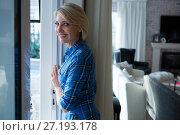 Купить «Happy woman standing in living room», фото № 27193178, снято 30 августа 2017 г. (c) Wavebreak Media / Фотобанк Лори