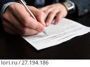 Купить «Бизнесмен подписывает документы сидя за столом», эксклюзивное фото № 27194186, снято 6 ноября 2017 г. (c) Игорь Низов / Фотобанк Лори