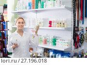 Купить «Smiling female shop assistant offering shampoo», фото № 27196018, снято 11 декабря 2017 г. (c) Яков Филимонов / Фотобанк Лори