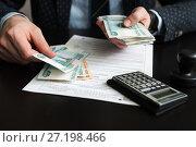 Купить «Индивидуальный предприниматель считает российские купюры для оплаты налога на фоне декларации», эксклюзивное фото № 27198466, снято 6 ноября 2017 г. (c) Игорь Низов / Фотобанк Лори