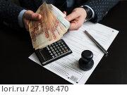 Купить «Бизнесмен подсчитывает деньги для оплаты налога на фоне декларации на вменённый доход», эксклюзивное фото № 27198470, снято 6 ноября 2017 г. (c) Игорь Низов / Фотобанк Лори