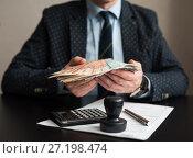 Купить «Предприниматель готовит деньги для оплаты налогов на фоне декларации на вменённый доход», эксклюзивное фото № 27198474, снято 6 ноября 2017 г. (c) Игорь Низов / Фотобанк Лори
