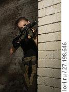 Купить «A girl with a submachine gun fires», фото № 27198646, снято 20 августа 2017 г. (c) Дмитрий Черевко / Фотобанк Лори