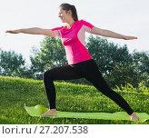Купить «Adult female in pink T-shirt is practicing yoga», фото № 27207538, снято 10 июня 2017 г. (c) Яков Филимонов / Фотобанк Лори