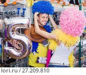 Купить «Family couple preparing for fest and choosing clown wigs», фото № 27209810, снято 11 апреля 2017 г. (c) Яков Филимонов / Фотобанк Лори