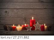 Купить «Christmas decoration with red candles on wooden background», фото № 27211882, снято 14 ноября 2017 г. (c) Майя Крученкова / Фотобанк Лори