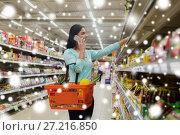 Купить «customer with food basket and smartphone at store», фото № 27216850, снято 2 ноября 2016 г. (c) Syda Productions / Фотобанк Лори