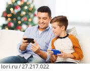 Купить «happy father and son with smartphones at christmas», фото № 27217022, снято 24 октября 2015 г. (c) Syda Productions / Фотобанк Лори