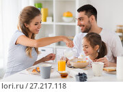 Купить «happy family having breakfast at home», фото № 27217118, снято 19 октября 2017 г. (c) Syda Productions / Фотобанк Лори
