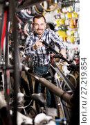 Купить «Man considers bicycle handlebar in store», фото № 27219854, снято 27 июня 2019 г. (c) Яков Филимонов / Фотобанк Лори