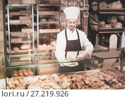 Купить «Favorable male pastry maker demonstrating croissant», фото № 27219926, снято 26 января 2017 г. (c) Яков Филимонов / Фотобанк Лори