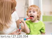Купить «Happy child boy brushing teeth near mirror in bathroom. His mother monitoring accuracy and time of cleaning action with hourglass.», фото № 27220354, снято 20 ноября 2017 г. (c) Оксана Кузьмина / Фотобанк Лори