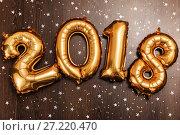 Купить «Bright metallic gold balloons figures 2018, Christmas, New Year Balloon with glitter stars on dark wood table background», фото № 27220470, снято 19 ноября 2017 г. (c) Сергей Тимофеев / Фотобанк Лори