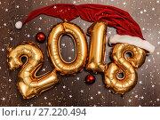 Купить «Bright metallic gold balloons figures 2018, Christmas, New Year Balloon with glitter stars on dark wood table background», фото № 27220494, снято 19 ноября 2017 г. (c) Сергей Тимофеев / Фотобанк Лори