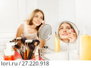 Купить «Beautiful young woman using facial cleansing brush», фото № 27220918, снято 3 июня 2017 г. (c) Сергей Новиков / Фотобанк Лори