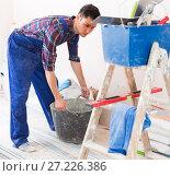 Купить «Craftsman is going to mix putty», фото № 27226386, снято 21 мая 2017 г. (c) Яков Филимонов / Фотобанк Лори